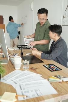 Dwóch kreatywnych projektantów wybierających kolory do nowego projektu