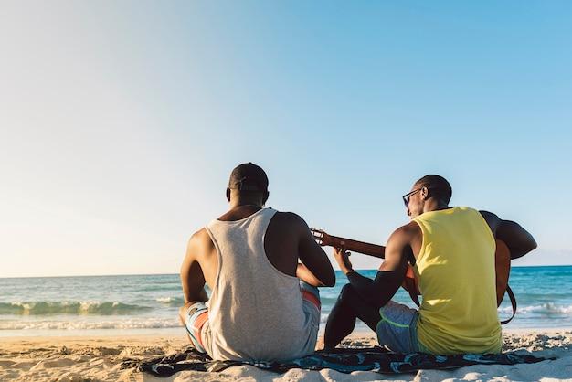 Dwóch kubańskich przyjaciół bawi się na plaży z gitarą. koncepcja przyjaźni.