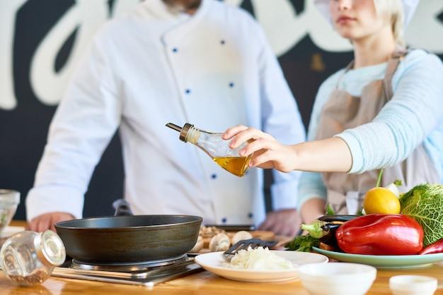 Dwóch kucharzy dodających oliwę z oliwek do naczynia z bliska