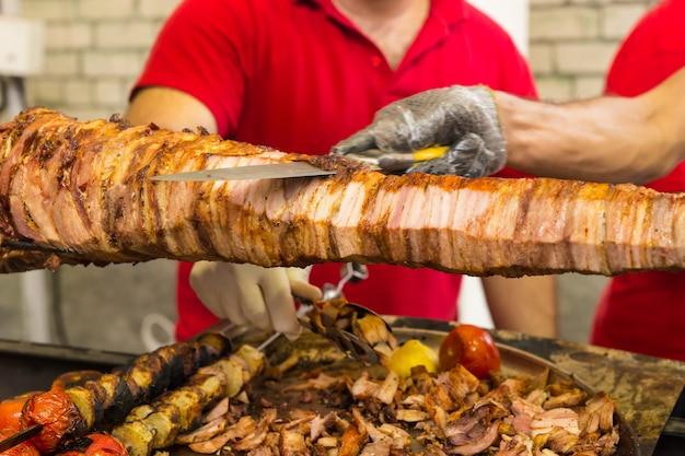 Dwóch kucharzy kroi pieczeń na rożnie nad ogniskiem grillowym za pomocą ostrego noża kuchennego do krojenia cienkich plastrów na bufet lub dania na wynos