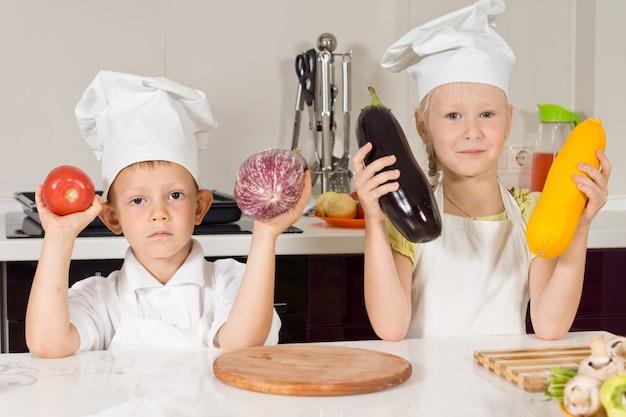 Dwóch kucharzy posiadających duże warzywa w kuchni. patrząc na aparat.