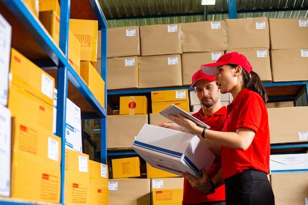 Dwóch kurierów sprawdza i przygotowuje pudełko do wysyłki do klienta.