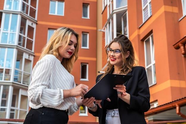 Dwóch ładnych agentów nieruchomości stojących w pobliżu domu na sprzedaż na świeżym powietrzu