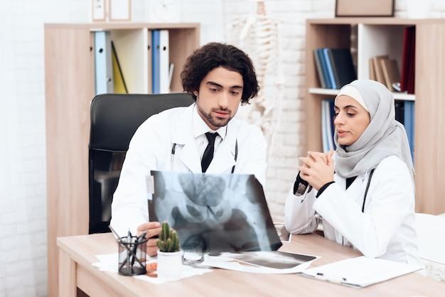Dwóch lekarzy bada prześwietlenie chorego pacjenta.