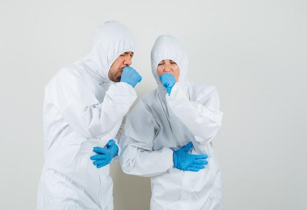 Dwóch lekarzy kaszlących w kombinezonach ochronnych