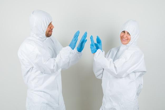 Dwóch lekarzy klaszczących w dłonie w kombinezonach ochronnych