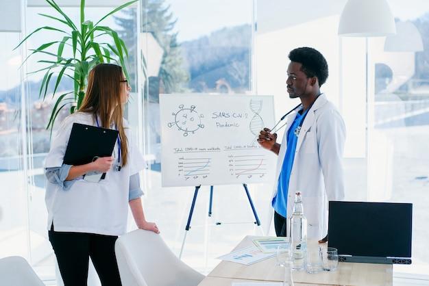 Dwóch lekarzy komunikuje się w sali konferencyjnej w szpitalu. afrykańscy męscy i caucasian żeńscy studenci medycyny przy pokojem konferencyjnym przy nowożytną kliniką.