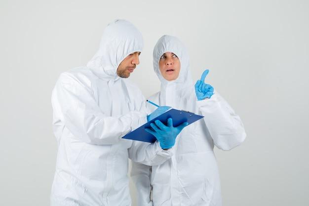 Dwóch lekarzy omawia wyniki badań laboratoryjnych w kombinezonie ochronnym