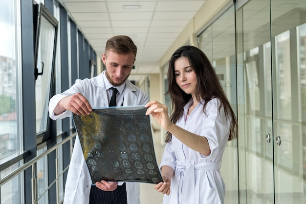 Dwóch lekarzy omawia wyniki obrazów rentgenowskiego rezonansu magnetycznego mózgu pacjenta w szpitalu. praca w zespole