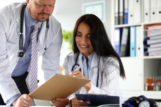 Dwóch lekarzy omawiających ważne dokumenty przypiętych do podkładki