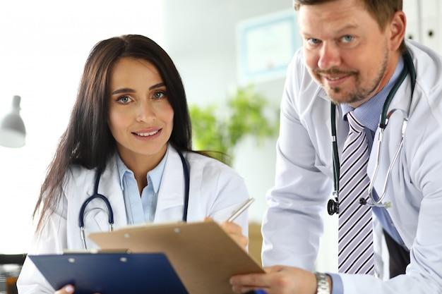 Dwóch lekarzy omawiających ważne dokumenty przytwierdzono do podkładki