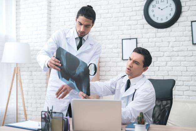 Dwóch lekarzy patrzy na zdjęcie rentgenowskie w gabinecie lekarskim.