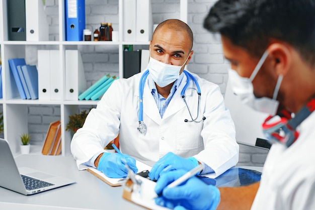 Dwóch lekarzy płci męskiej omawiających swoją pracę w gabinecie