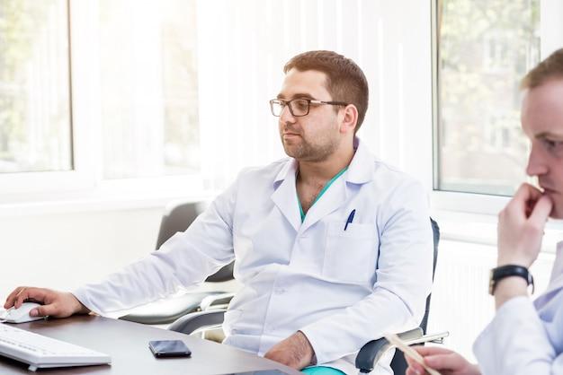 Dwóch lekarzy posiadających radę lekarską w szpitalu. omawianie zagadnień medycznych.