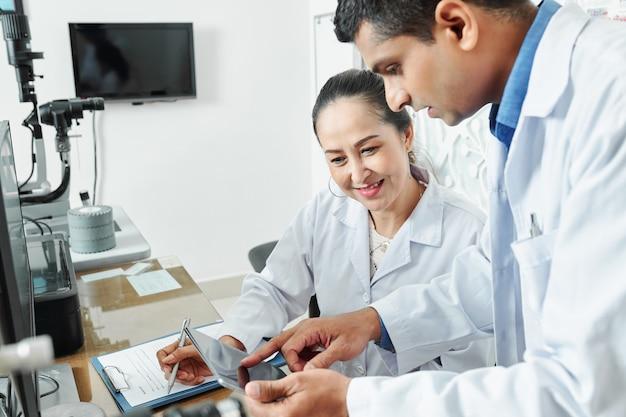 Dwóch lekarzy pracujących z komputerem typu tablet