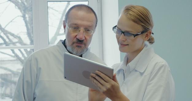 Dwóch lekarzy prowadzi profesjonalną rozmowę za pomocą panelu dotykowego