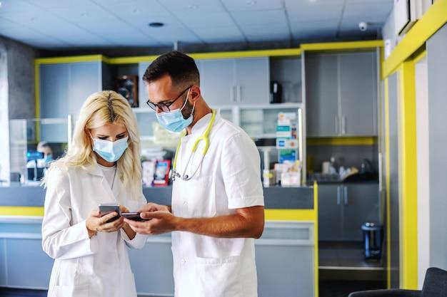 Dwóch lekarzy stojących w szpitalu na przerwie i korzystających z telefonów komórkowych.