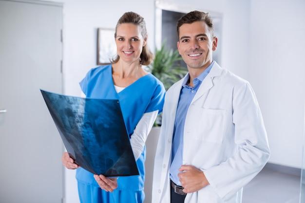 Dwóch lekarzy stojących z prześwietleniem pacjenta w korytarzu szpitala