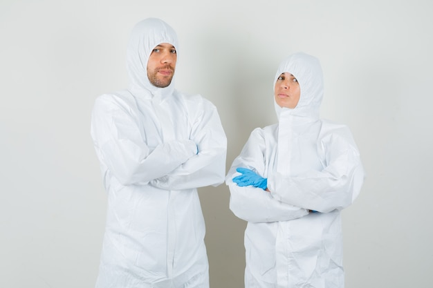 Dwóch lekarzy stojących ze skrzyżowanymi rękami w kombinezonach ochronnych