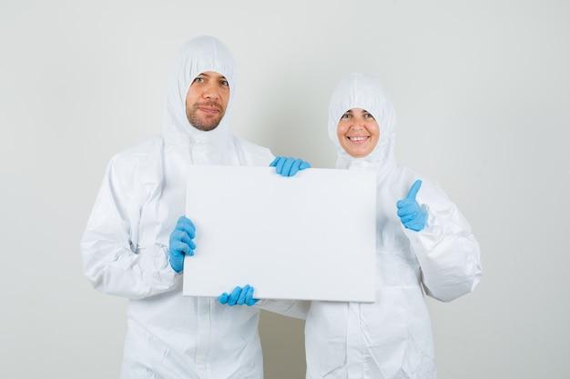 Dwóch lekarzy trzymając puste płótno, pokazując kciuk w kombinezonach ochronnych