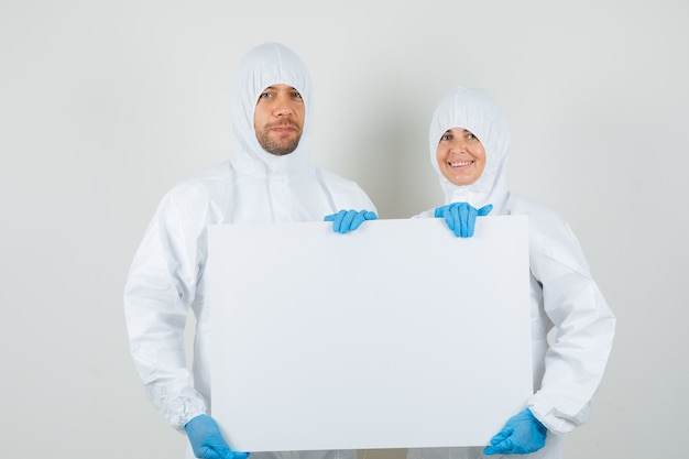 Dwóch lekarzy trzymających puste płótno w kombinezonach ochronnych, rękawiczkach i wyglądających wesoło