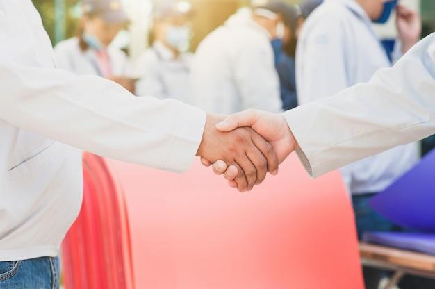 Dwóch lekarzy uścisnąć dłonie i inne osoby w tle noszącą maskę