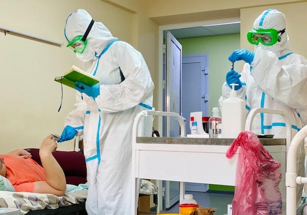 Dwóch lekarzy w kombinezonach ochronnych na oddziale pacjentów z koronawirusem
