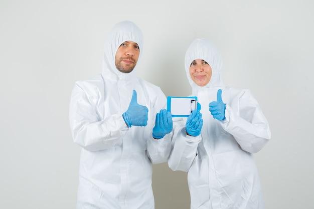 Dwóch lekarzy w kombinezonach ochronnych, rękawiczkach, trzymając mini schowek