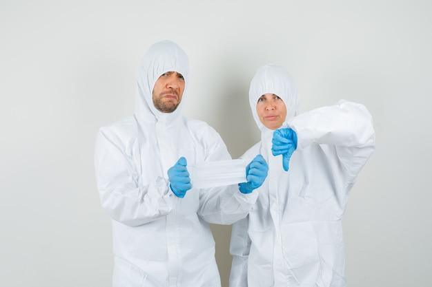 Dwóch lekarzy w kombinezonach ochronnych, rękawiczkach trzymających maskę medyczną i pokazujących kciuk w dół