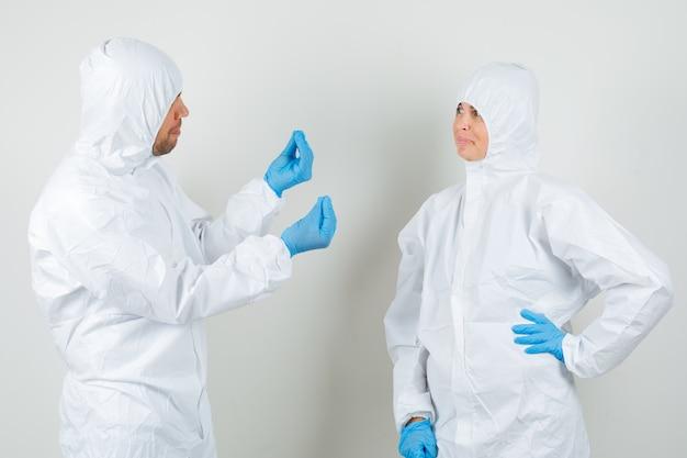 Dwóch lekarzy w kombinezonach ochronnych, w rękawiczkach dyskutujących o czymś i wyglądających wesoło
