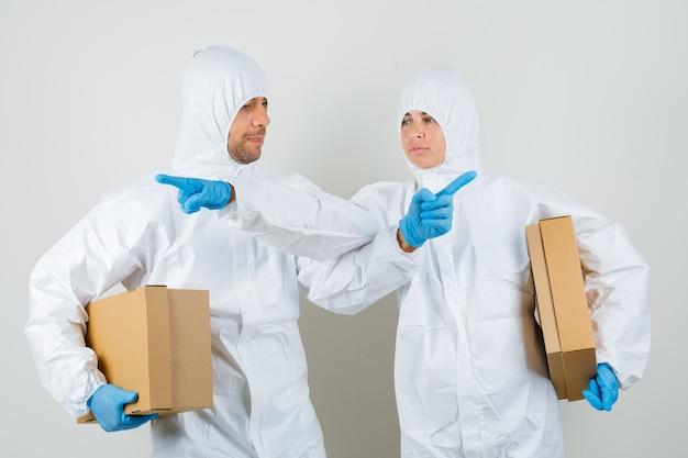 Dwóch lekarzy w kombinezonach ochronnych, w rękawiczkach trzymających kartony