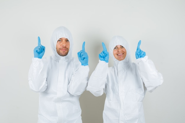 Dwóch lekarzy w kombinezonach ochronnych, w rękawiczkach wskazujących palcami w górę i wyglądających na zadowolonych