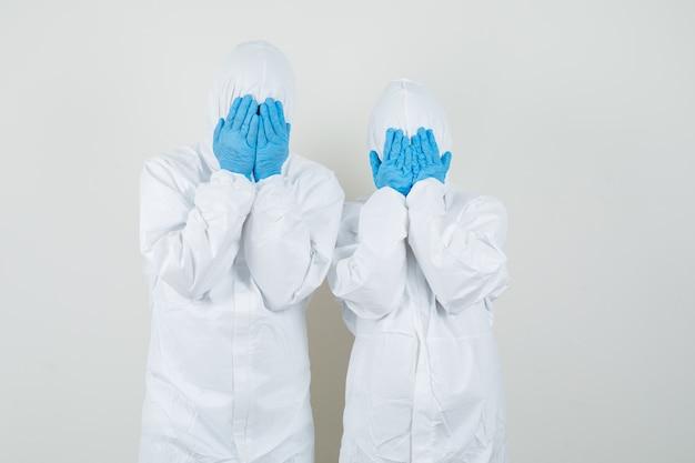 Dwóch lekarzy w kombinezonach ochronnych, w rękawiczkach zakrywających twarz i wyglądających na przestraszonych