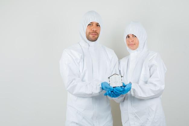 Dwóch lekarzy w kombinezonie ochronnym, rękawiczkach trzyma model domu i wygląda wesoło