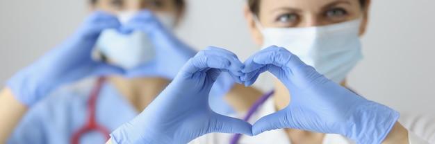 Dwóch lekarzy w maskach medycznych i rękawiczkach gumowych przedstawiających serce rękami