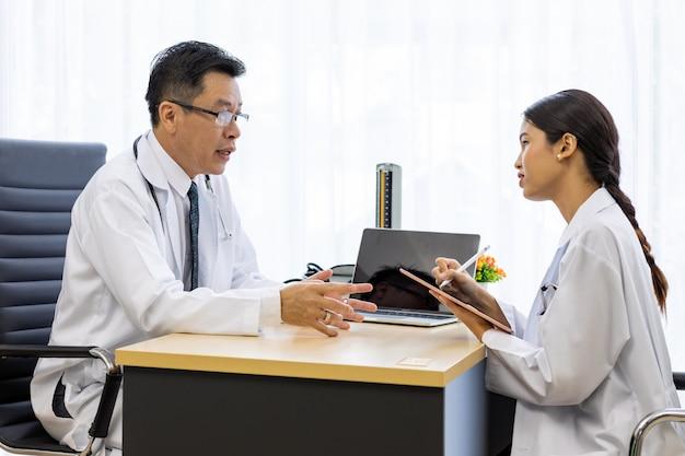Dwóch lekarzy w szpitalu omawia diagnozy pacjenta