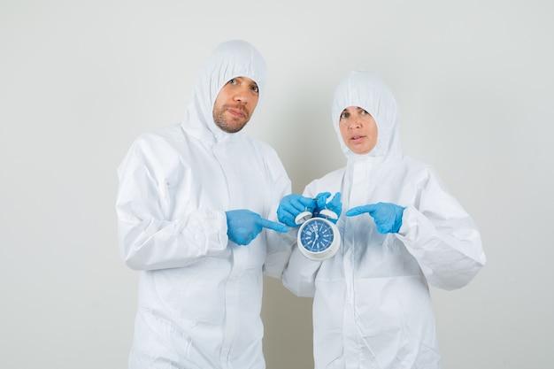 Dwóch lekarzy, wskazując na budzik w kombinezonie ochronnym
