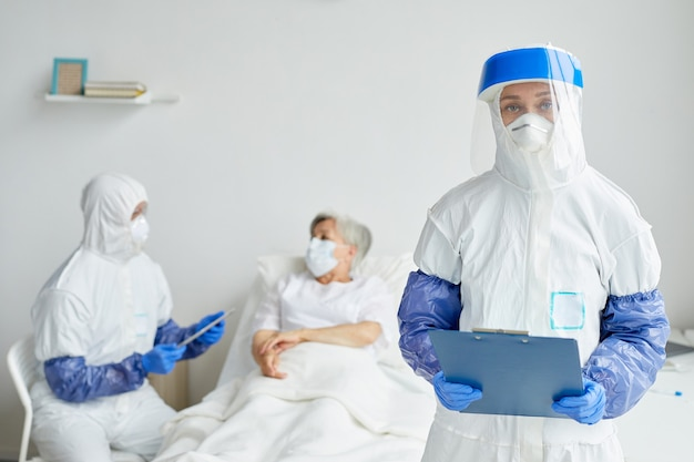 Dwóch lekarzy zawodowych w kombinezonach ochronnych z rękawiczkami, maskami i okularami, pracujących z wiekowym pacjentem na oddziale chorób zakaźnych