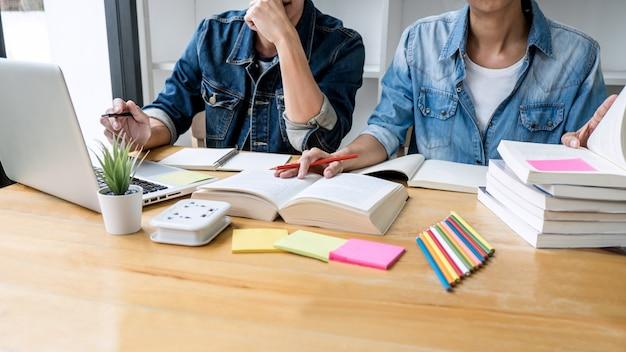 Dwóch licealistów lub kolegów z klasy pomaga przyjaciołom odrabiać zadania domowe w klasie