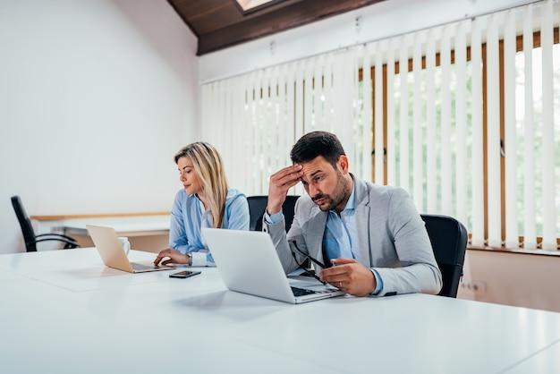 Dwóch ludzi biznesu działa na laptopach w biurze coworking.