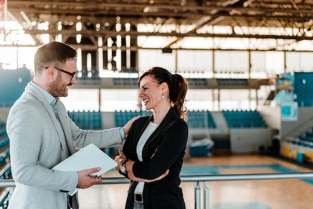 Dwóch ludzi biznesu o spotkaniu na arenie sportowej.