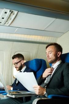 Dwóch ludzi biznesu pracujących w samolocie