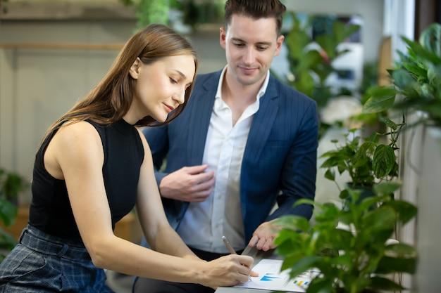 Dwóch ludzi biznesu siedzi w kawiarni nad nowym projektem za pomocą laptopa. młody bizneswoman robienie notatek i biznesmen pracy na komputerze przenośnym.