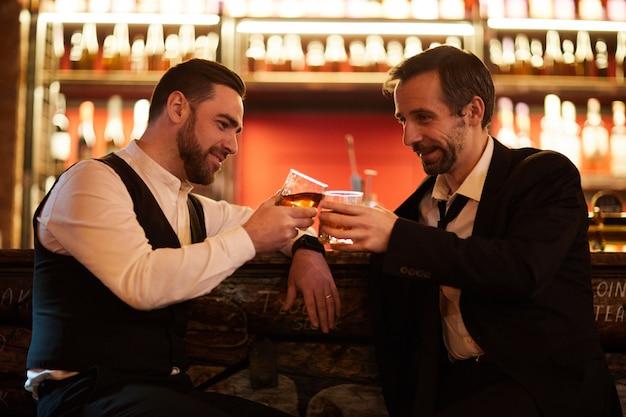 Dwóch ludzi biznesu świętuje w barze