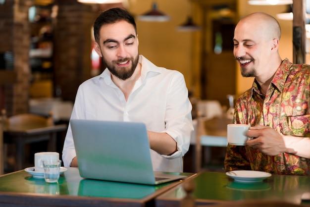 Dwóch ludzi biznesu za pomocą laptopa podczas spotkania w kawiarni. pomysł na biznes.