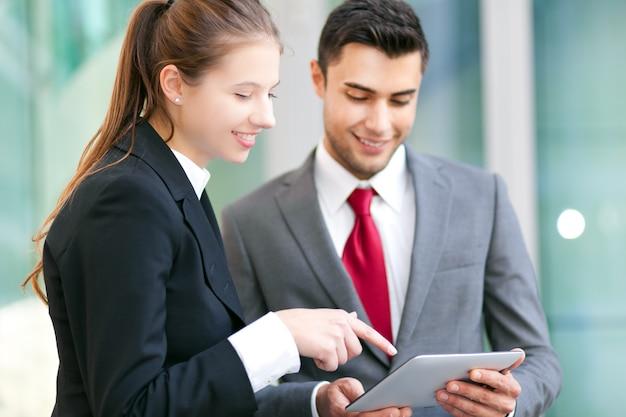Dwóch ludzi biznesu za pomocą tabletu w miejskim otoczeniu
