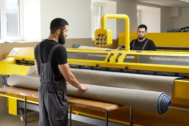 Dwóch ludzi obsługujących profesjonalny sprzęt do czyszczenia w pralni do czyszczenia dywanów