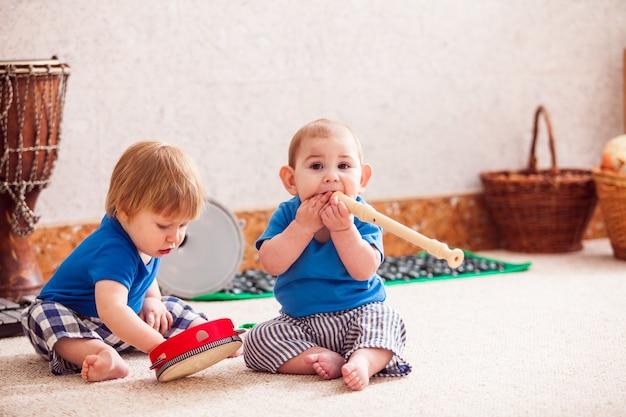 Dwóch małych chłopców entuzjastycznie bawiących się różnymi instrumentami muzycznymi
