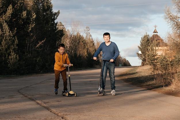 Dwóch małych chłopców jeździ na hulajnogach. ciepły letni lub wiosenny dzień. bracia bawią się razem. pojęcie przyjaźni.
