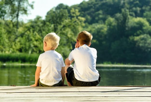 Dwóch małych chłopców siedzi na molo na brzegu rzeki. przyjaźni i braterstwa. widok z tyłu